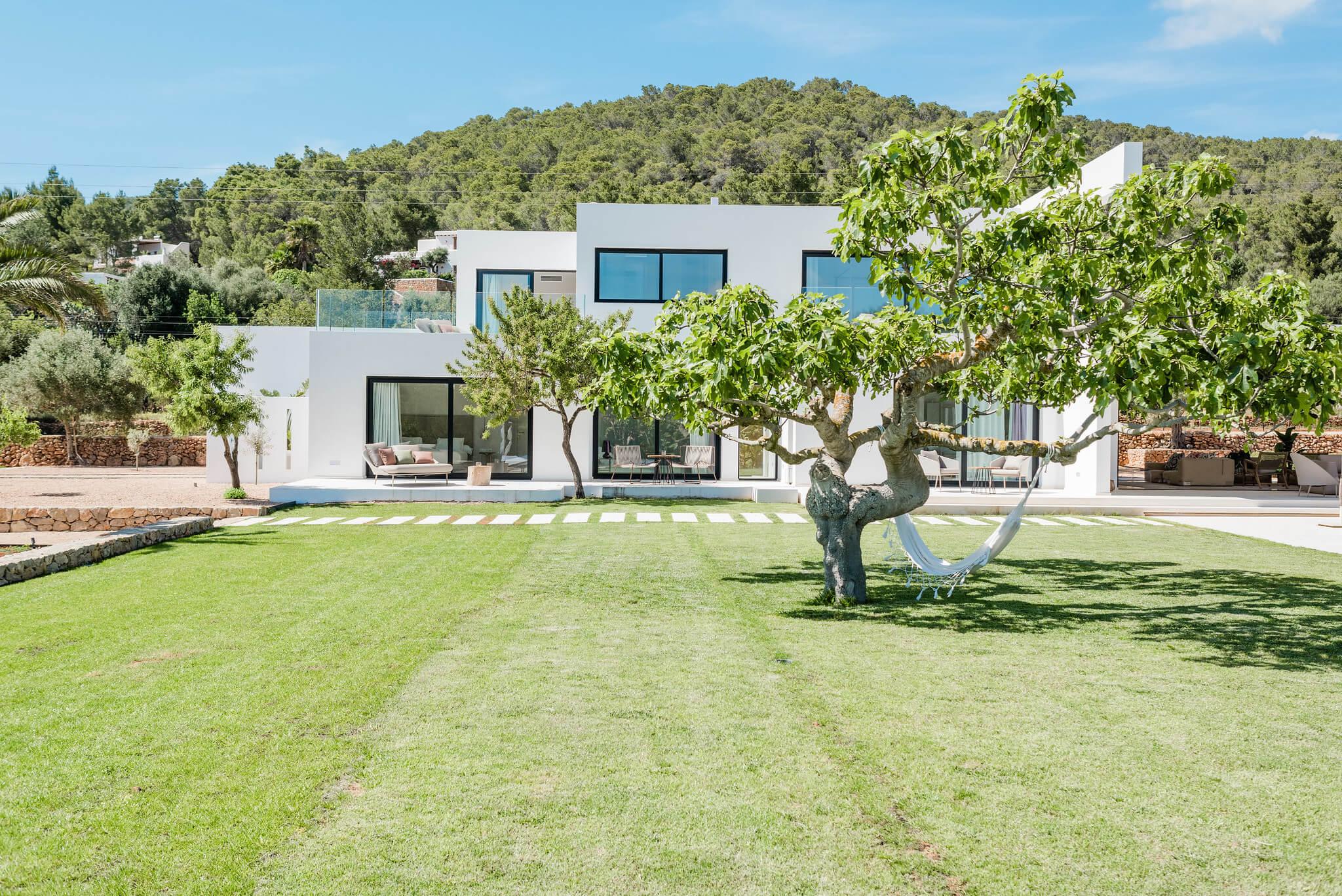 https://www.white-ibiza.com/wp-content/uploads/2020/06/white-ibiza-villas-can-carmen-exterior-across-lawn.jpg